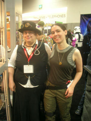 A picture of me in a Viper Pilot costume with a woman who's wearing a steampunk outfit and has a NASAthulhu sitting on her hat. The NASAthulhu holds a leash that is attached to her next